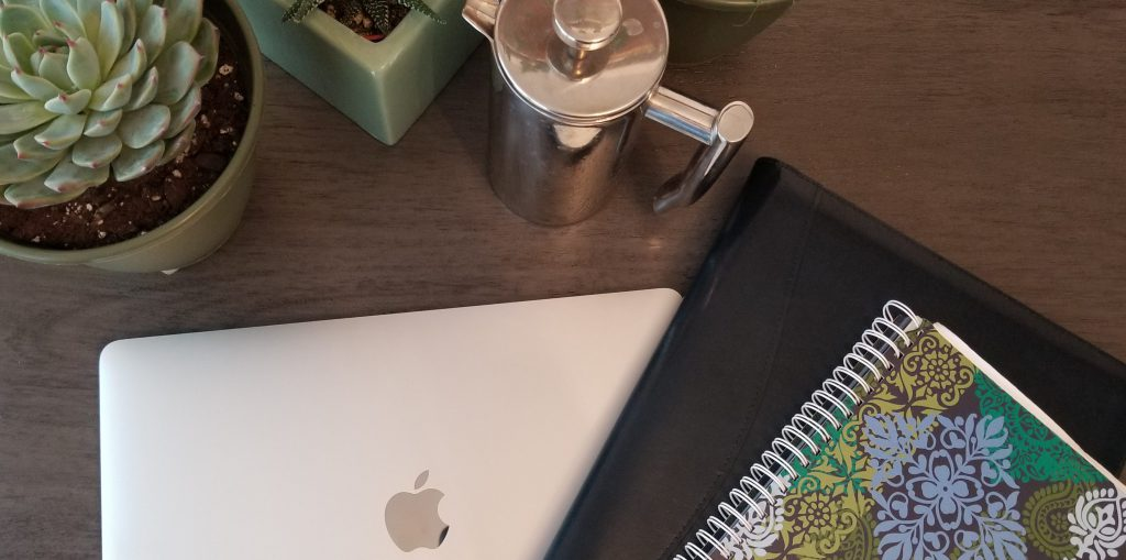 An aerial view of a desk setup featuring an Apple laptop computer under a blue portfolio and small paisley notebook. Succulents and a steel french press peek out from the top of the frame.