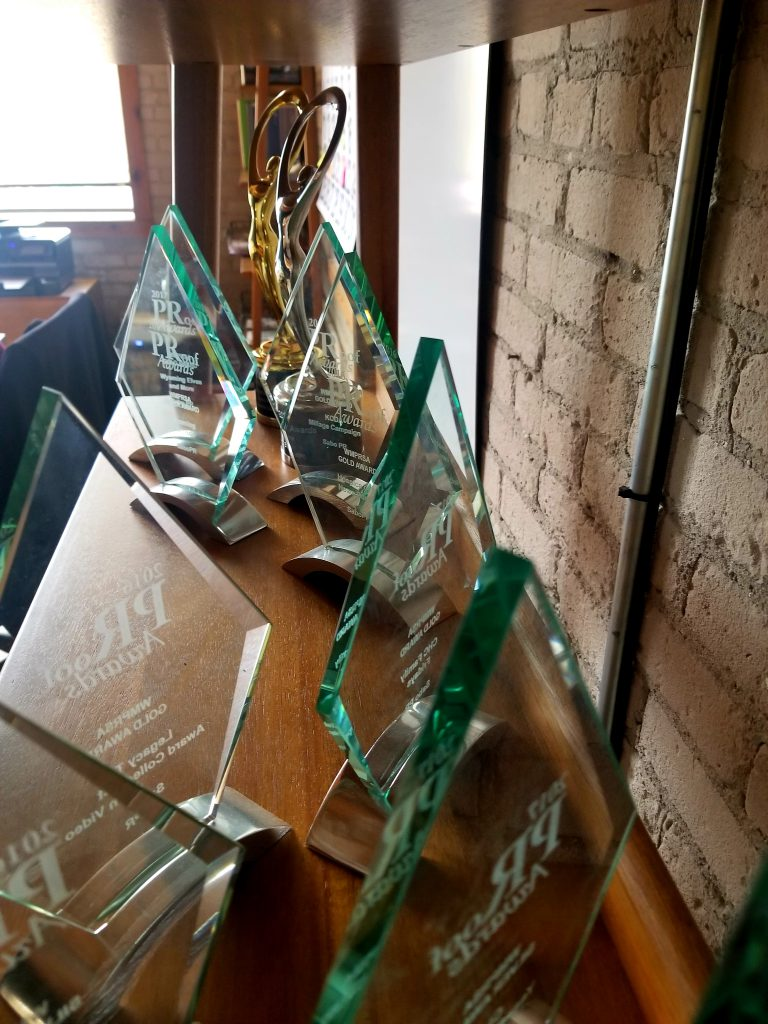 Crystal-clear glass awards from the WMPRSA 2016 PRoof Awards line a shelf.