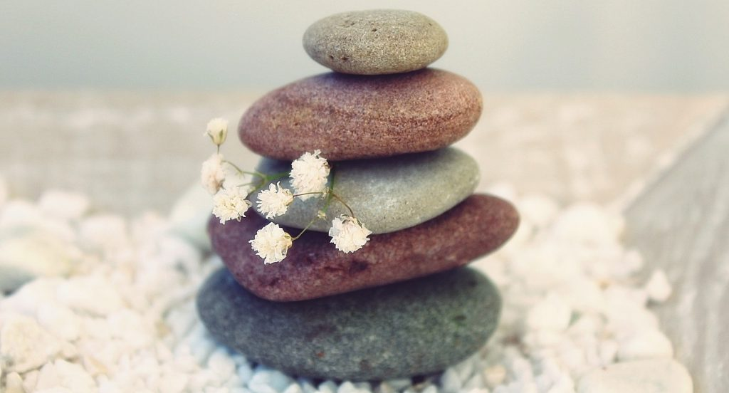 Five different colored rocks are stacked on top of each other, balancing on a bed of small white stones. A sprig of Baby's Breath is peeking out from the middle of the stack. The stones get smaller toward the top.