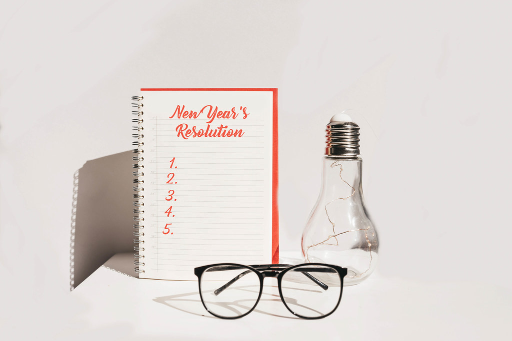 A blank New year's resolutions list. Desk with notebook, glasses and decorative light bulb.