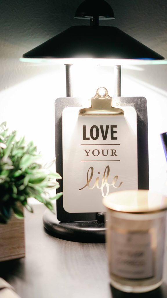"""""""Love Your Life"""" office decor with a plant and candle to complement blog post on mental health and self-care"""