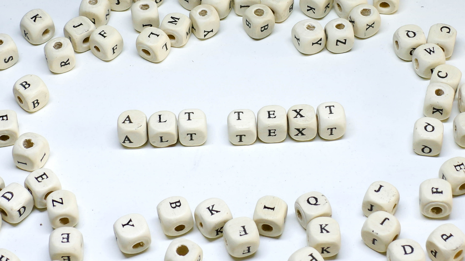 Square letter beads arranged to spell out alt text with other letter beads surrounding the words. Alternative text, or image descriptions, increase accessibility for readers who have visual impairments.