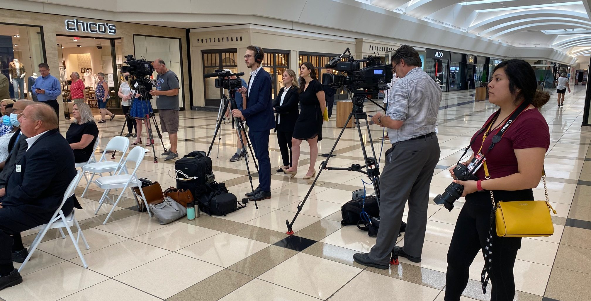 Hunter, Chiara and Lisa behind a camera for a mall announcement, next two TV reporter and a photographer in advance of media interviews
